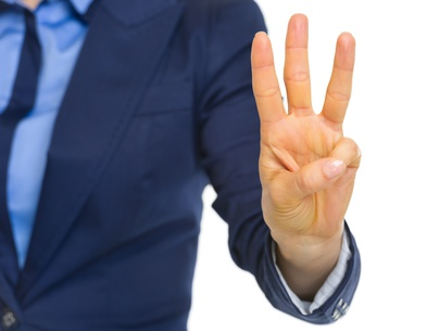 Closeup on business woman showing 3 fingers